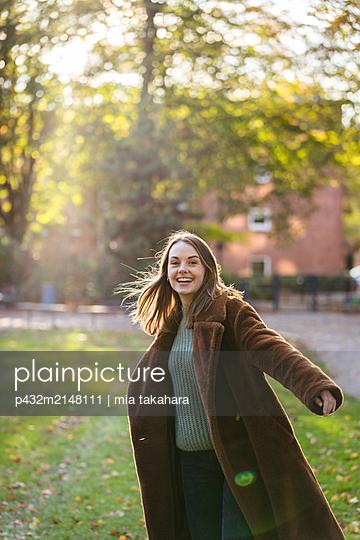 Glückliche junge Frau im Park - p432m2148111 von mia takahara