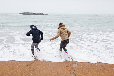 Playful teenage brother and daughter playing in winter ocean surf - p1023m2024281 by Sam Edwards