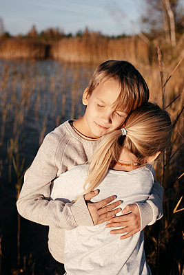 Portrait of boy hugging his little sister in autumnal nature - p300m2140310 by Ekaterina Yakunina