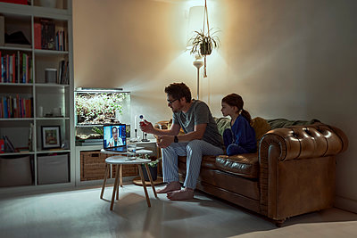 Sick girl sitting by father discussing telemedicine with doctor over video call through laptop in living room at home - p300m2188553 by Eloisa Ramos