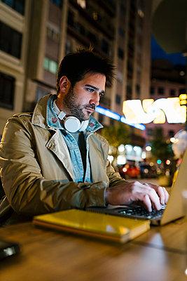 Mid adult man with headphones using laptop while sitting at sidewalk cafe - p300m2251078 by Ezequiel Giménez