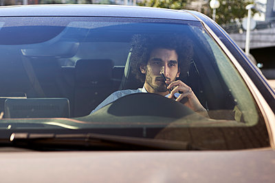Thoughtful entrepreneur holding smart phone while sitting in car - p300m2268291 by Veam