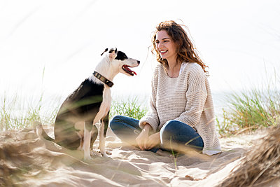 Smiling woman looking at dog while sitting on sand during vacations - p300m2286949 by Steve Brookland