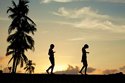 Silhouette boys walking along ledge against tranquil sunset sky - p301m2123120 by Nik West