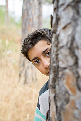 Scared boy hiding behind a tree  - p794m2031650 by Mohamad Itani