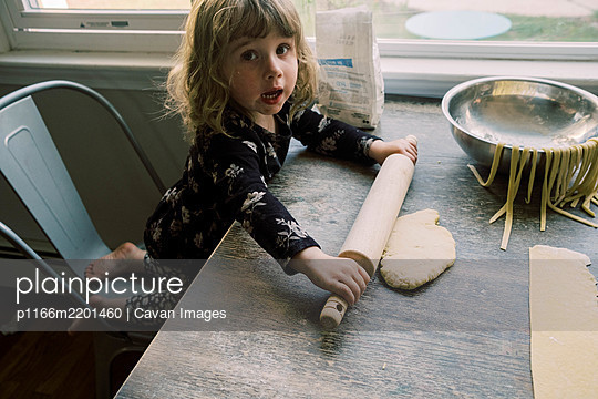 A toddler girl rolling out pasta dough on a table - p1166m2201460 by Cavan Images