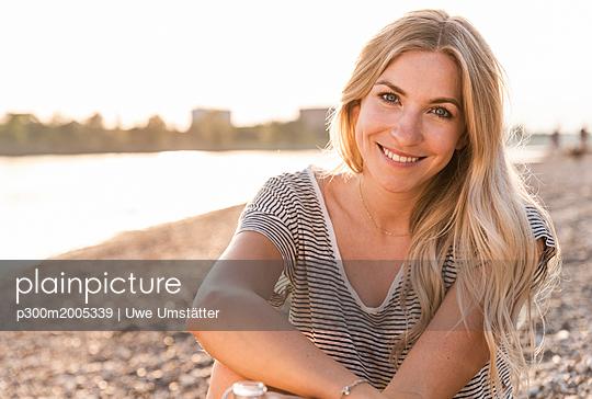 Portrait of blond woman at riverside in the evening - p300m2005339 von Uwe Umstätter