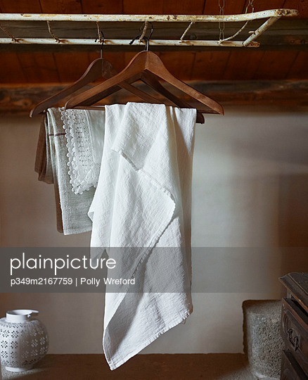 White linen and lace on wooden clothes hangers in Sicilian home - p349m2167759 by Polly Wreford