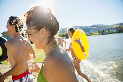 Young friends on sunny summer lake beach - p1192m1183773 by Hero Images