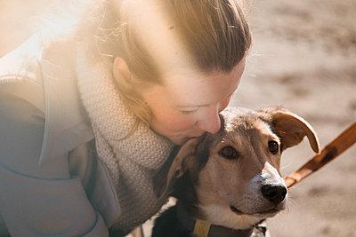 Junge Frau küsst ihren Hund - p1642m2222243 von V-fokuse
