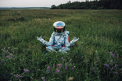 Spaceman exploring nature, sitting in meadow, meditating - p300m2030494 by Vasily Pindyurin
