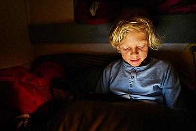 Boy using tablet in bed - p300m2070710 by Stefan Schütz