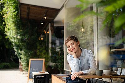 Portrait of smiling businesswoman at a cafe - p300m2140541 by Kniel Synnatzschke