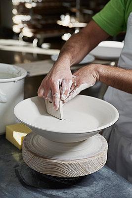 A potter molding a bowl on a potter's wheel - p301m844169f by Paul Hudson