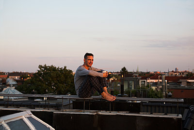 Man holding coffee mug on roof - p341m2008665 by Mikesch