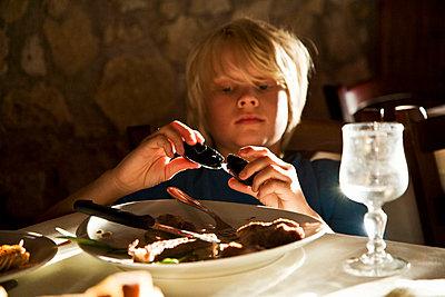 Boy eating mussels in restaurant - p528m713703 by Kari Kohvakka