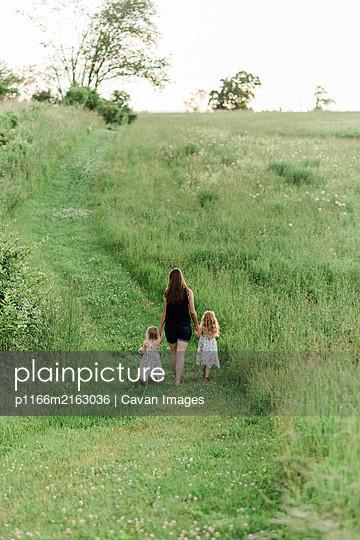 A mom and her girls walking through a meadow and picking  wildflowers. - p1166m2163036 by Cavan Images