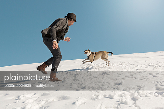 Man playing with dog in winter, throwing snow - p300m2004639 von realitybites