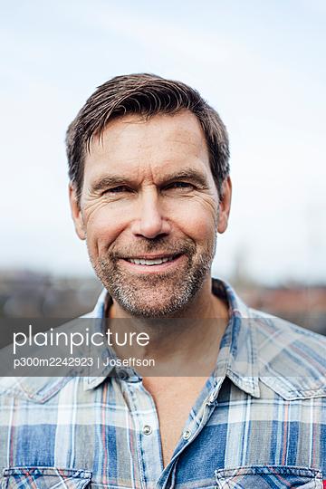 Smiling mature man against sky - p300m2242923 by Joseffson
