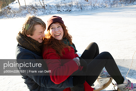 Loving couple having fun while sledding on ice - p300m2287631 by Frank van Delft