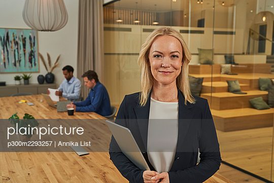 Smiling blond businesswoman holding digital tablet while standing in board room - p300m2293257 by Annika List
