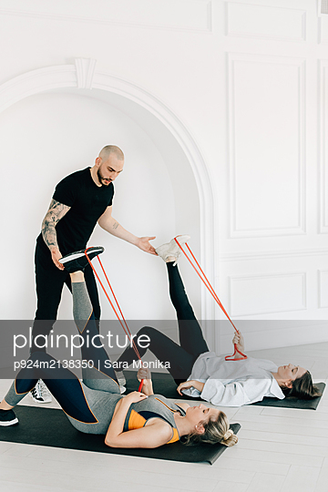 Fitness instructor teaching women using resistance band in studio - p924m2138350 by Sara Monika