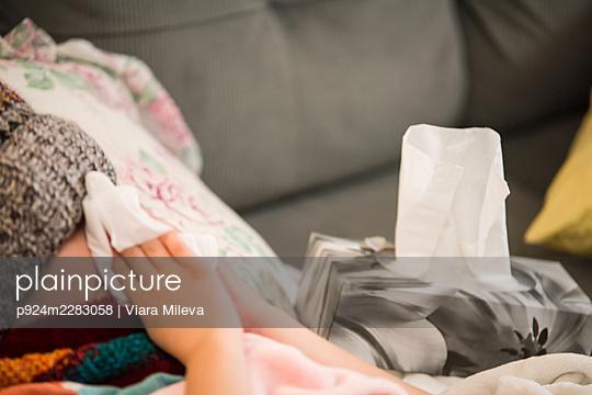 Canada, Ontario, Boy in knit hat blowing nose on sofa - p924m2283058 by Viara Mileva