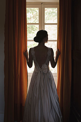 Bride standing at the window - p1150m1514930 by Elise Ortiou Campion