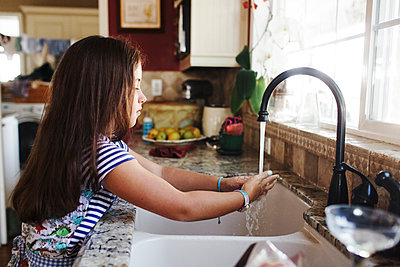Side view of girl washing hands at kitchen sink - p1166m1509724 by Cavan Images
