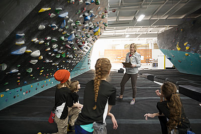 Female instructor teaching girl rock climber students at climbing wall in climbing gym - p1192m1560049 by Hero Images