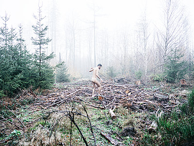 Naked man walks stumbles over clearing in the fog - p1267m2258811 by Jörg Meier