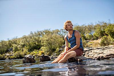 Junger Mann badet seine Füße im Fluss - p1355m1574210 von Tomasrodriguez