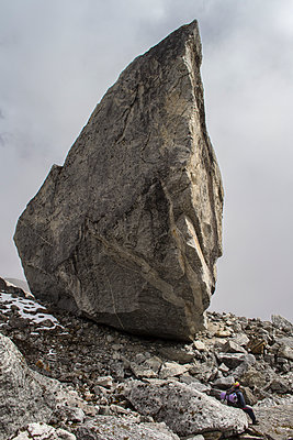 Mountain hiker alongside colossal boulder - p1369m1425619 by Chris Hooton