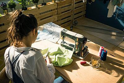 Back view of fashion designer at work in her studio - p300m1581450 von Robijn Page