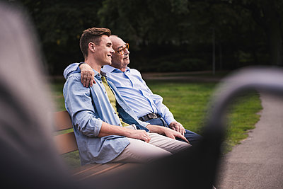 Senior man and grandson relaxing together on a park bench - p300m2144630 by Uwe Umstätter