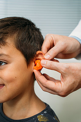 Male audiologist putting hearing air in child's ear at clinic - p300m2243869 by Manu Padilla Photo