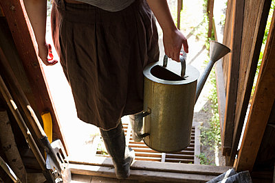 Waist down view of woman carrying watering can in shed doorway - p429m1417780 by Chuvashov Maxim