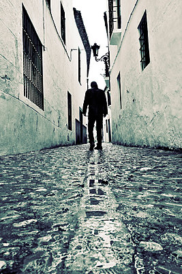Rearview man walking up old street in Ronda, Spain - p597m2063505 by Tim Robinson