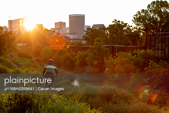 Mountain biker at sunrise with Richmond skyline in the background. - p1166m2269641 by Cavan Images