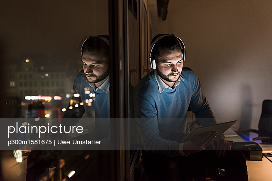 Businessman sitting on window sill in office at night using tablet and headphones - p300m1581675 von Uwe Umstätter