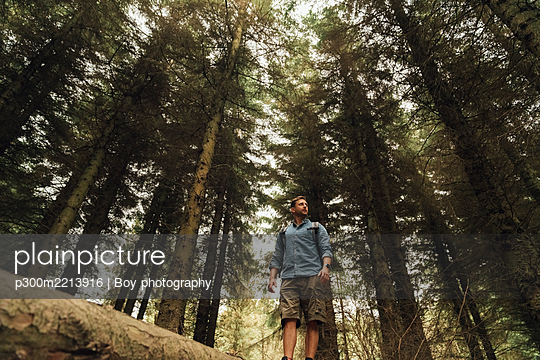 Male explorer looking away while standing on log against trees in forest - p300m2213916 by Boy photography
