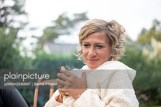 Woman holding coffee cup while sitting on chair at back yard - p300m2240047 by Bernd Friedel