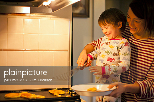 Mother and son cooking pancakes together. - p456m897997 by Jim Erickson