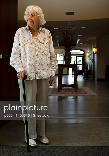 Older Caucasian woman standing with cane in retirement home - p555m1408816 by Shestock