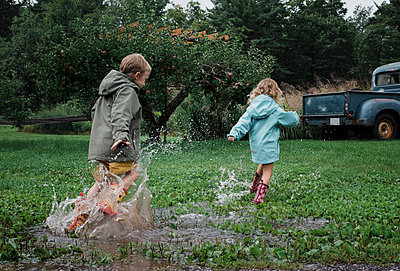 Playful siblings splashing water in puddle at apple orchard - p1166m2024807 by Cavan Images