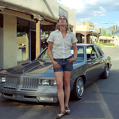 A woman poses next to an old fancy car in Santa Fe - p1610m2186027 by myriam tirler
