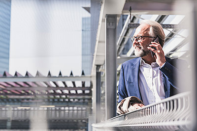Smiling mature businessman in the city on cell phone - p300m1587975 by Uwe Umstätter