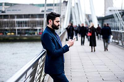 Businessman leaning against footbridge railing reading smartphone text, London, UK - p429m1135196f by Bonfanti Diego