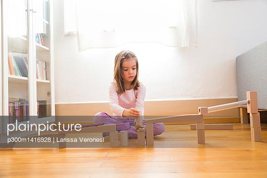 Little girl crouching on floor building marble run with building bricks - p300m1416928 by Larissa Veronesi