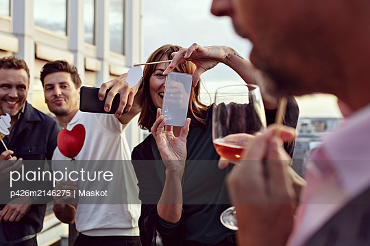 Business colleagues making memories while photographing with smart phones at after work celebrations on terrace - p426m2146275 by Maskot